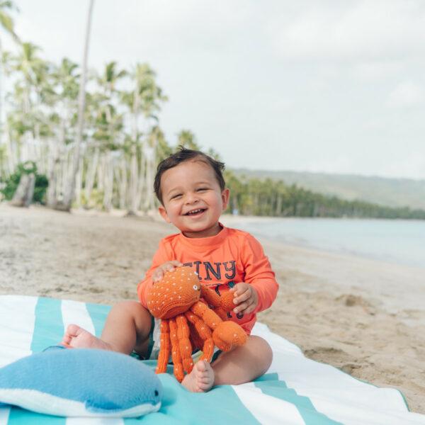 Kind sitzt mit seiner Kuscheltier Krabbe am Meer