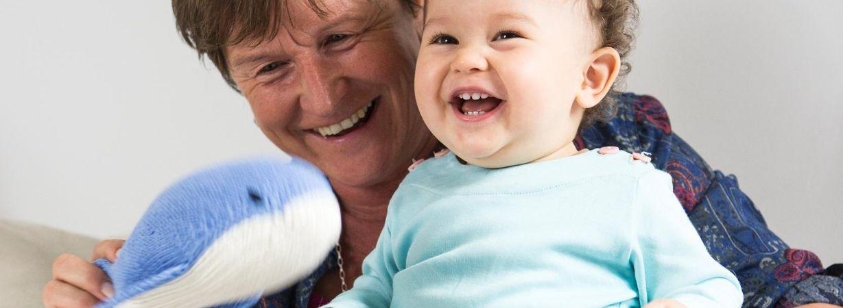 Lachende Oma mit Enkelkind und Kuschel-Wal