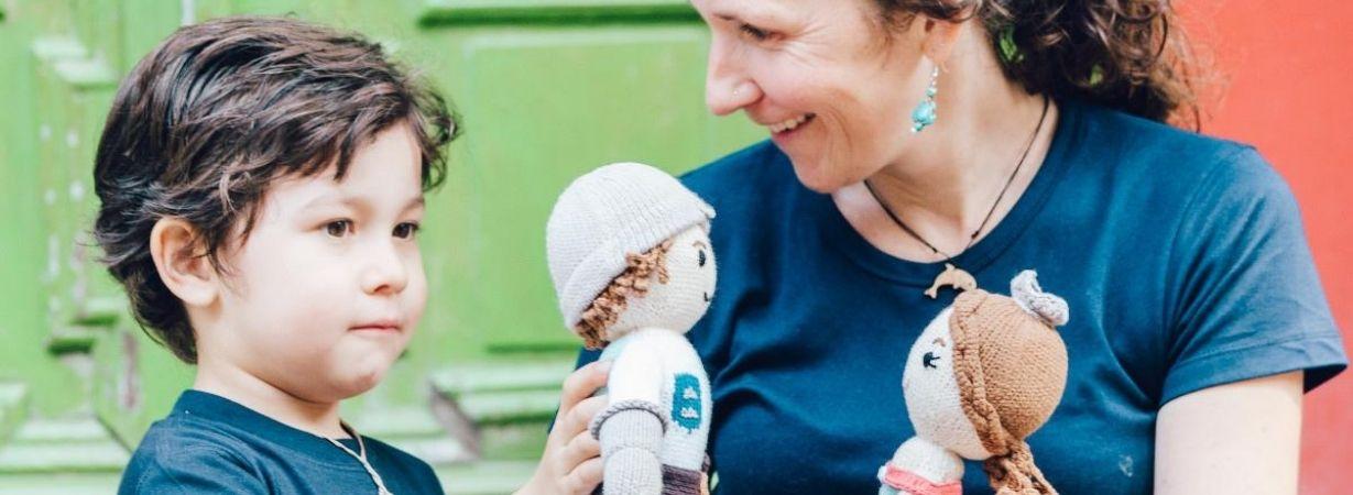 Mutter und Sohn spielen mit Puppen aus Bio Baumwolle