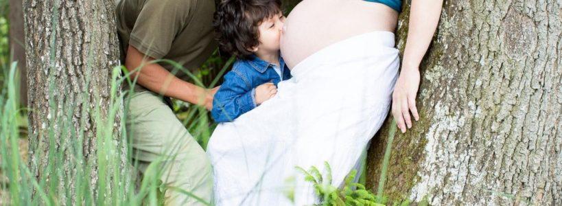 Großer Bruder küsst Babybauch