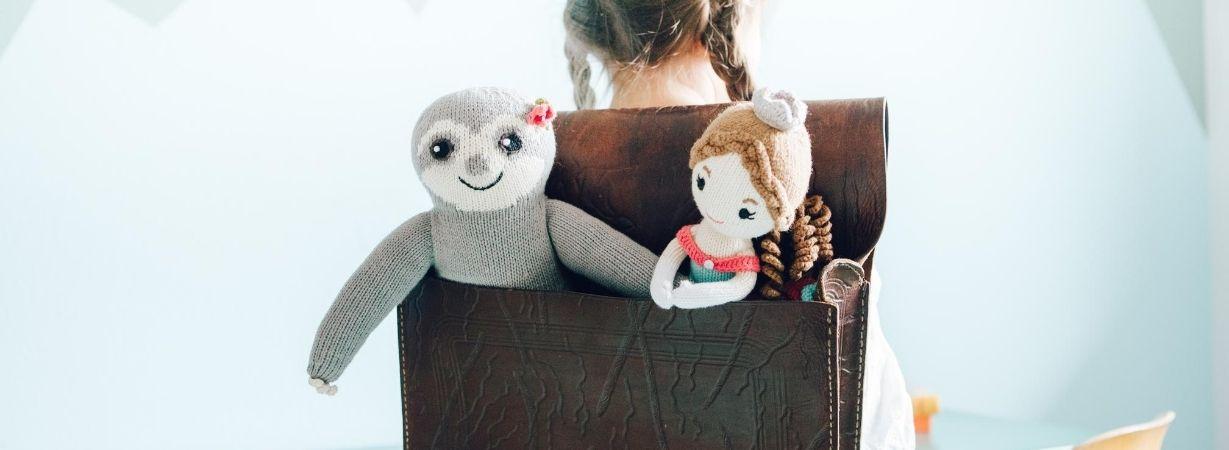 Mädchen trägt Schulranzen mit zwei Puppen darin