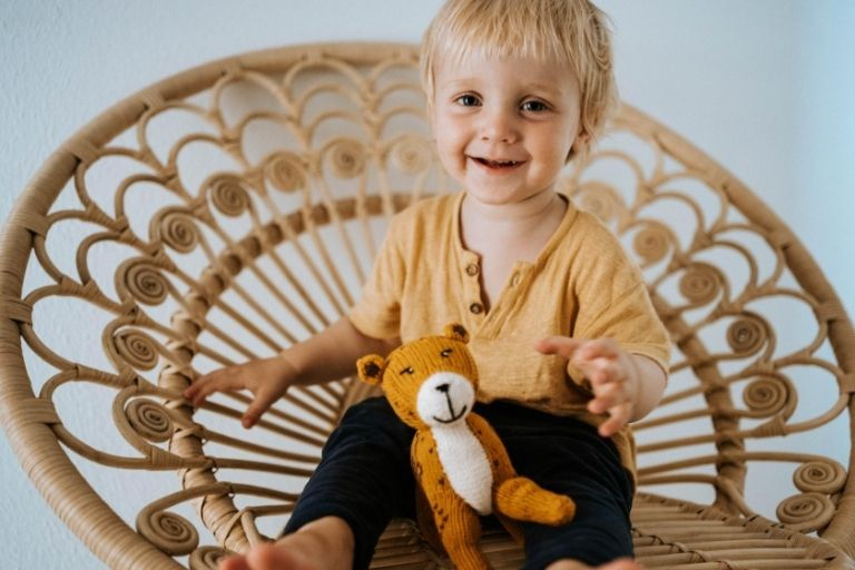 Lachendere Junge auf Korbstuhl spielt mit Kuscheltier Jaguar
