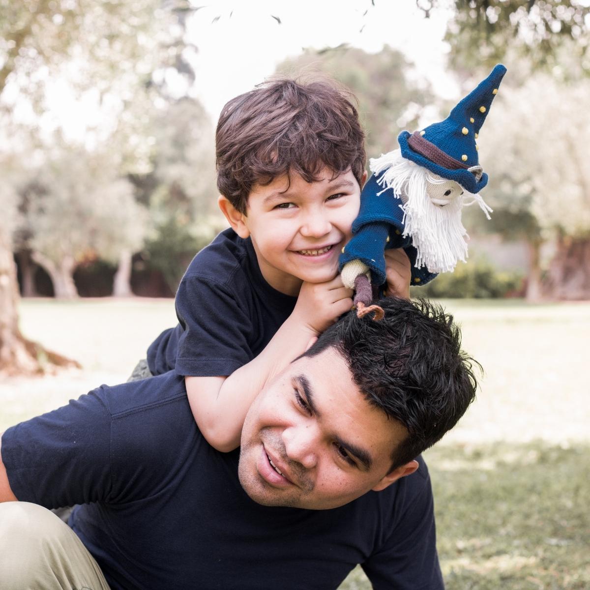 Papa und Sohn mit Puppe Zauberer Merlin